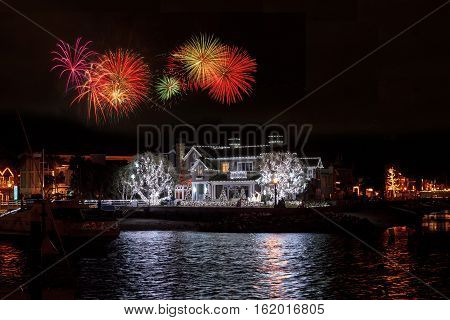 December 16, 2016 - Newport Beach, CA, USA: Fireworks over colorful holiday lights on sailboats and ships in the Balboa Harbor for the Newport Beach Christmas Boat Parade. Editorial use only.