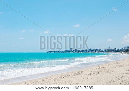 Beach with sand bay and a beautiful blue water ocean. City on the background on a beautiful sunny day. Holiday destination.