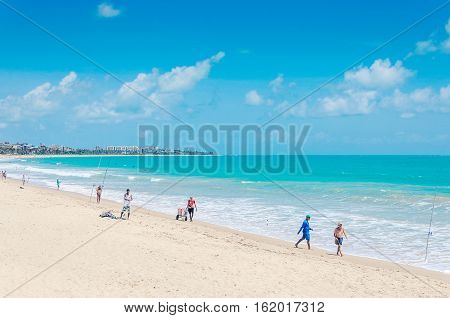 Joao Pessoa PB Brazil - December 8 2016: Beach of Joao Pessoa city with sand bay and a beautiful blue water ocean. People fishing by the sea on a sunny day. Holiday destination.