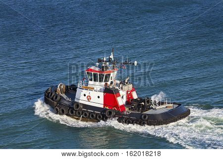 Red and White Tug Boat on the open ocean from above.