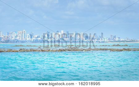 Sea with blue water with some rocks and background city. Beautiful background of coastal city Joao Pessoa PB - Brazil.