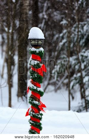Outside light pole decorated for Christmas with red ribbon and green garland in the snow.