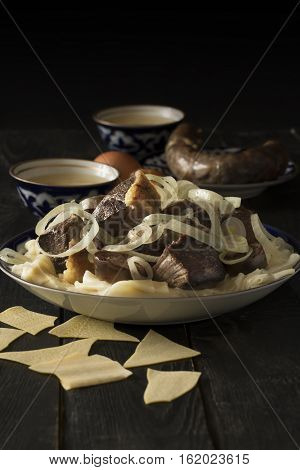 National Kazakh dish - Beshbarmak prepared with meat and pasta on the dark wooden table. Vertical orientation