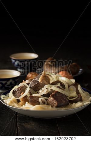 National Kazakh dish - Beshbarmak prepared with meat and pasta on the dark wooden table