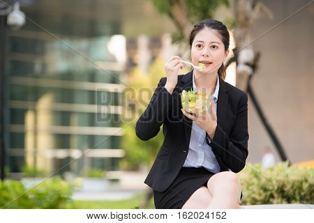 Beautiful Asian Business Woman Eating Salad On Park Bench