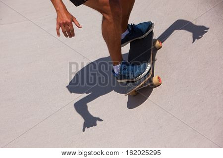 Skateboarder drive board on a ramp in skate park