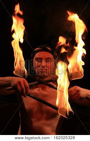Diabolic man with the fire torches isolated on the dark background