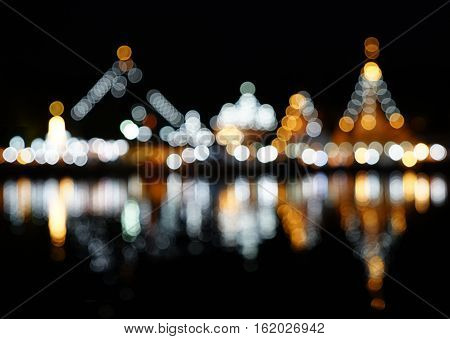 Abstract blurred bokeh light of Wat Chong Klang and Wat Chong Kham with water reflection Mae Hong Son Thailand