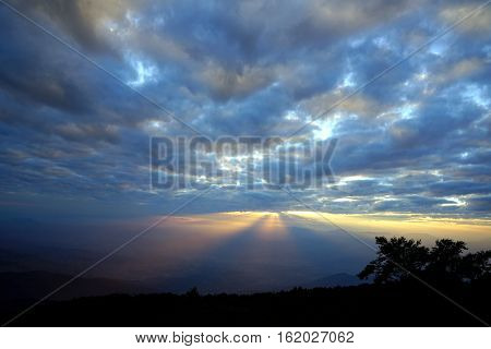 Mountain landscape with wave of fog and dark cloudy sky. Dreamy sunset on the top of mountain with the view into misty valley. Doi Inthanon National Park Chiang Mai Thailand