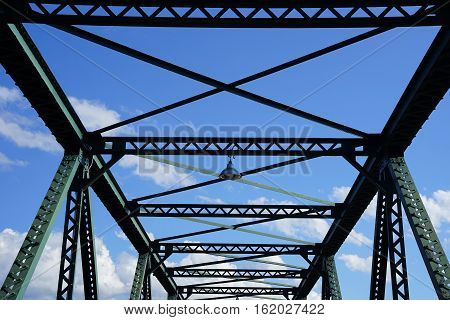 Steel structure support above the bridge on blue sky background