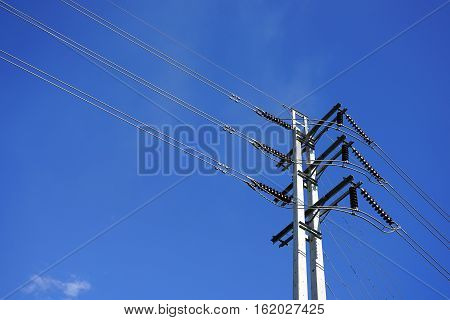 High voltage electric post with power line cables against blue sky