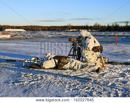 Sniper with a rifle and a spotter with optical equipment of observation in white camouflage cloaks on snowy terrain
