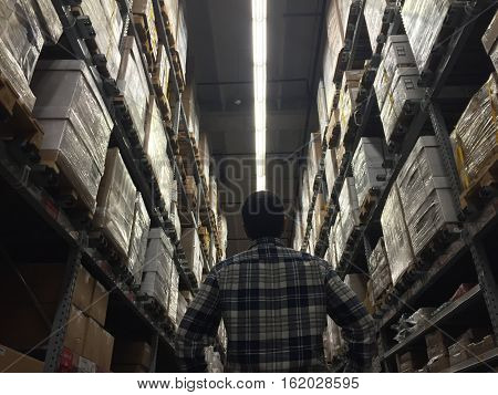 Business owner standing on warehouse inspecting packages before shipping