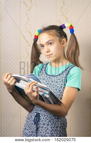 11 year old girl thoughtfully standing with a stack of books