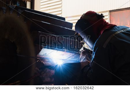 Industrial welding worker with safety protective mask in factory Gear weld repair in Shielded Metal Arc Welding Process.