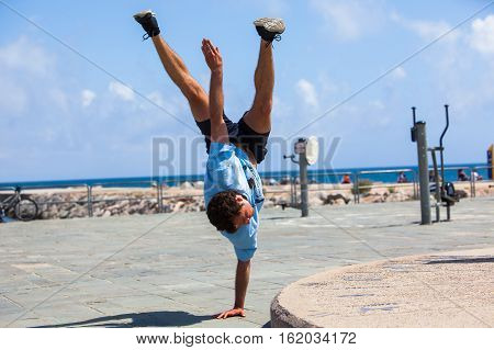 BARCELONA SPAIN - MAY 30 2016: YOUNG ATHLETE DOING ACROBATICS EXERCISES PARKOUR TRICKS ON STREAT AT LA BARCELONETA BEACH IN BARCELONA SPAIN - MAY 30 2016