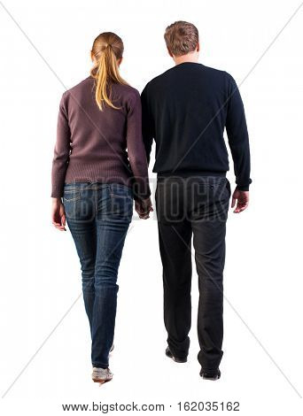 Back view of walking  young couple (man and woman). going beautiful friendly girl and guy in shorts together. young heterosexual couple in sweaters and jeans holding hands move slowly forward