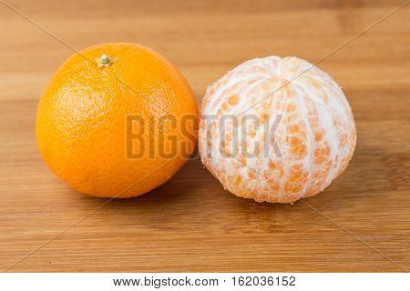 Two Navel Oranges One Peeled One Unpeeled Isolated On Wood Background