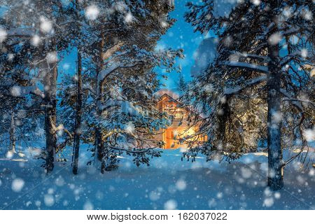 Winter fairytale night snowfall landscape - Wooden house with warm light in night snowy winter forest