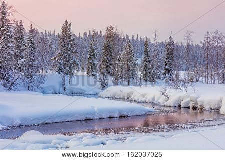 Winter evening landscape with forest and river, big snow and beautiful sundown colors