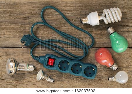 various lamps and multi-outlet extension cord on a wooden table