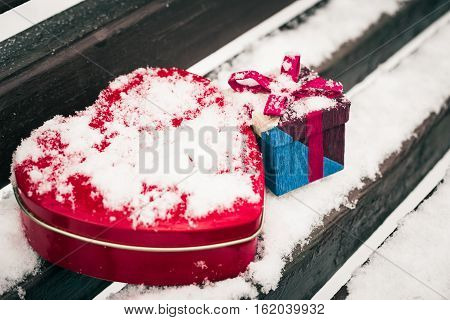 A gift box with red heart shaped tin box on a bench covered with snow