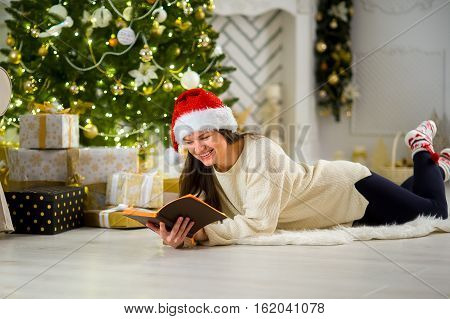 Cute girl the brunette in Santa's cap. Beautifully decorated Christmas tree stands nearby. Elegantly decorated Christmas tree stands nearby. Beautiful boxes with gifts under the Christmas tree.