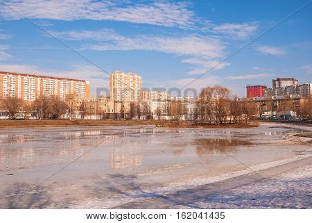 Frozen pond in the park of the modern city