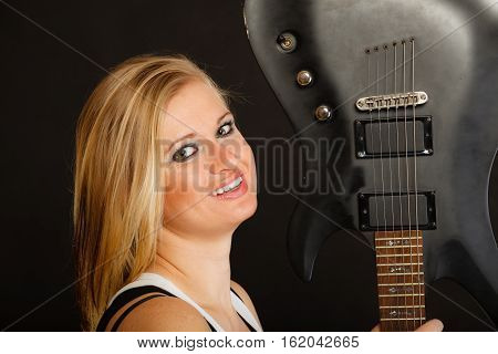 Music singing concept. Smiling blonde musically talented woman holding electric guitar on black background