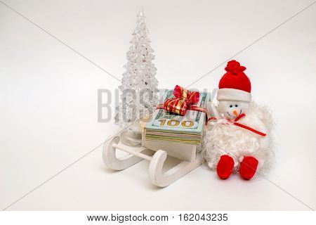 snowman on a sled driven by a stack of American Currency