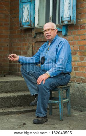 Portrait of elderly Ukrainian peasant sitting near his house and smoking cigarette