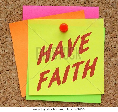 The words Have Faith in red text on a yellow sticky note pinned to a cork notice board