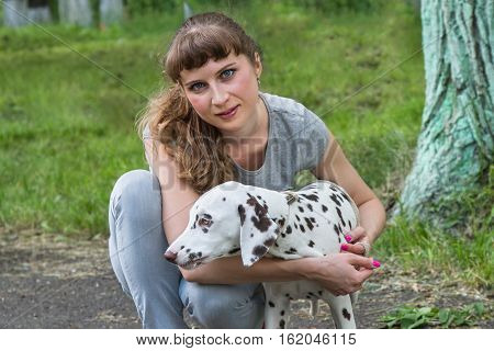Young girl with her dog Dalmatian .