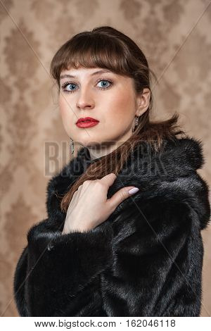 Portrait of a beautiful young girl in a black fur coat