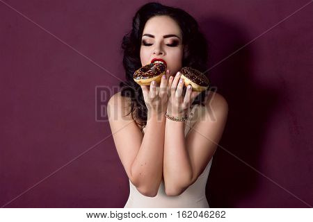young, beautiful, attractive, darkhaired woman with colorful, tasty, glazed doughnuts on marsala background