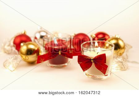 Red and white candles with red bow-knot, christmas toys and lights