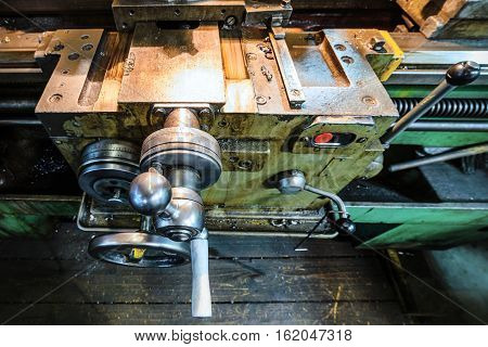 The carriage slide. Mechanical wheel carriage control. Vintage metal cutting lathe. The old mechanical cutting equipment.
