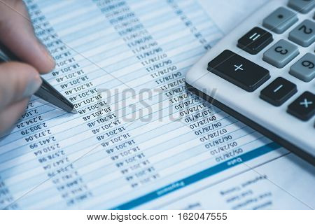 Accounting financial banking stock spreadsheet data with human hand holding pen and calculator in blue.