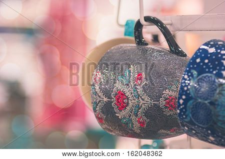 Tea cup cups in brown and blue hanging and waiting to be filled up with smooth and silky bokeh lights pink background. Concept for cozy warm family time