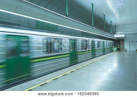 Subway train carts fast speed moving with motion blur, selective focus, empty station in green and blue. Concept for urban traveling, city public transport.