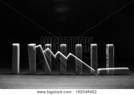 falling dominoes on a wooden table  double exposure
