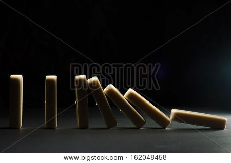 dominoes falling on each other with a dark background