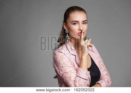 Woman requires silence. Young beautiful woman has put forefinger to lips as sign of silence