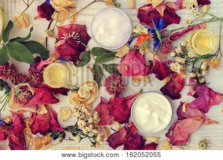 Aromatic botanical cosmetics. Dried flowers mixture, facial mask in sample jars, oils. Holistic herbal DIY skincare beauty hack. Retro pink toned.