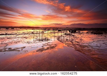 Sunrise skies reflecting on the exposed rock shelf at Long Reef Northern Beaches Australia