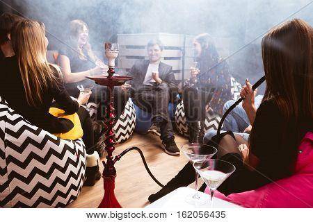 Group of young friends relaxing in shisha club-bar