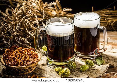 Couple beer mug with hop and pretzels on linen cloth on wooden table