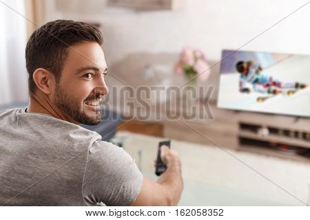 Excited man switch TV to ski rading by remote control