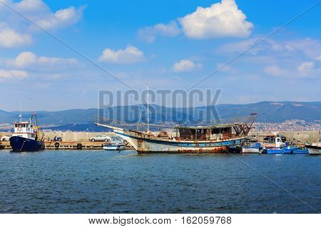 Nesebar Bulgaria - August 30 2013: Old ship boats yachts and launches standing at the pier in the port of the old town of Nessebar on the Black Sea coast. Sunny summer day.