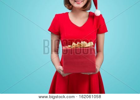 Mrs. Santa. Beautiful Young Asian Woman In Santa's Hat Holding A Gift Isolated On Blue.